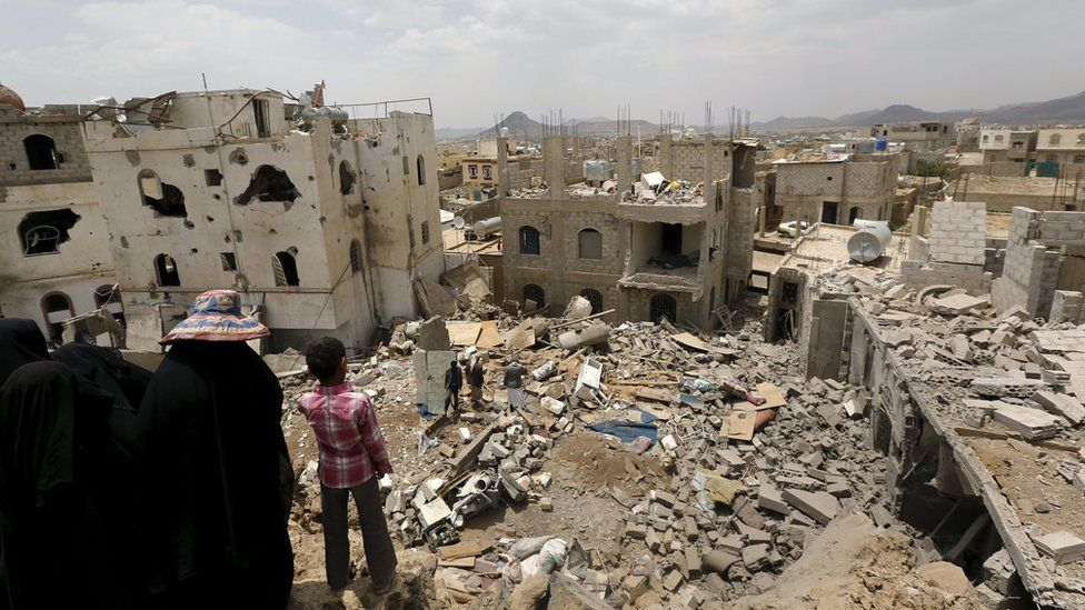 People look at the rubble of houses destroyed by a Saudi-led air strike in Yemen's capital, Sana'a