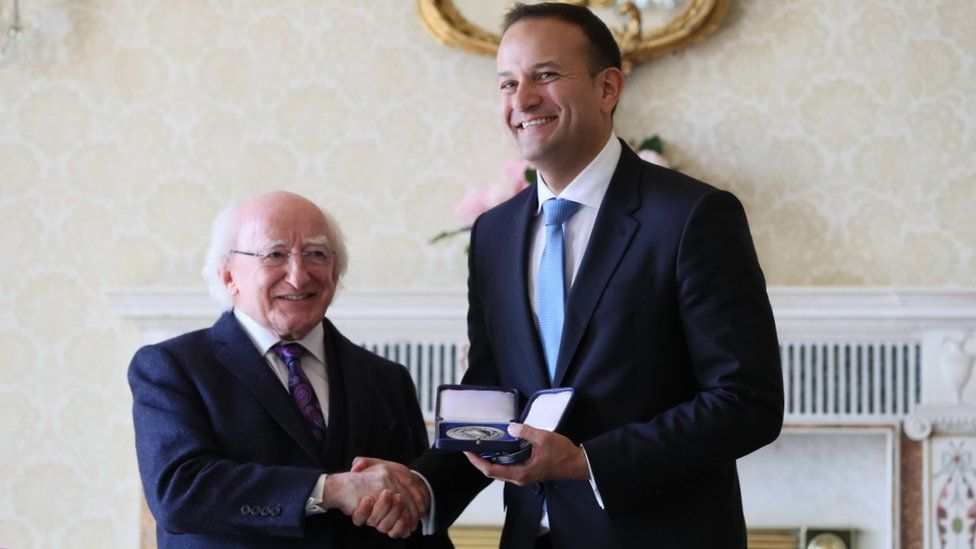 Michael D Higgins presents Leo Varadkar with the seals of office