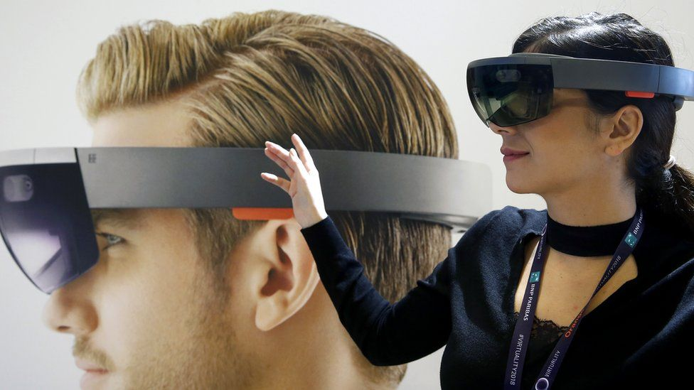 A visitor tries a virtual reality (VR) headset Microsoft HoloLens during the Virtuality Paris 2018 show, 8 February 2018