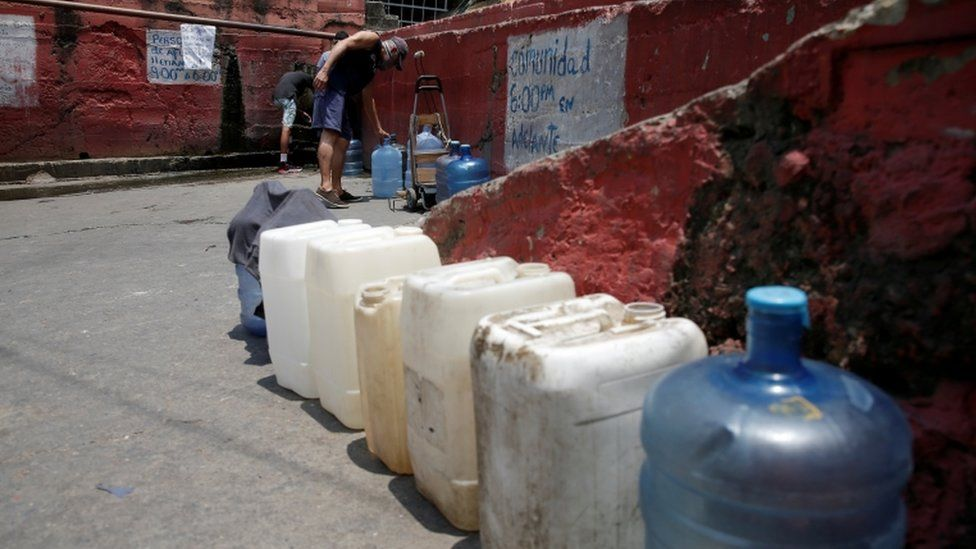 A man fills plastic containers with water from a pipe in a street of a slum during a nationwide quarantine due to coronavirus disease (COVID-19) outbreak in Caracas, Venezuela April 2, 2020