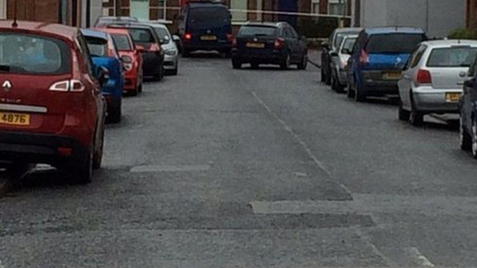The van that the prison officer was travelling in can be seen at the end of the street