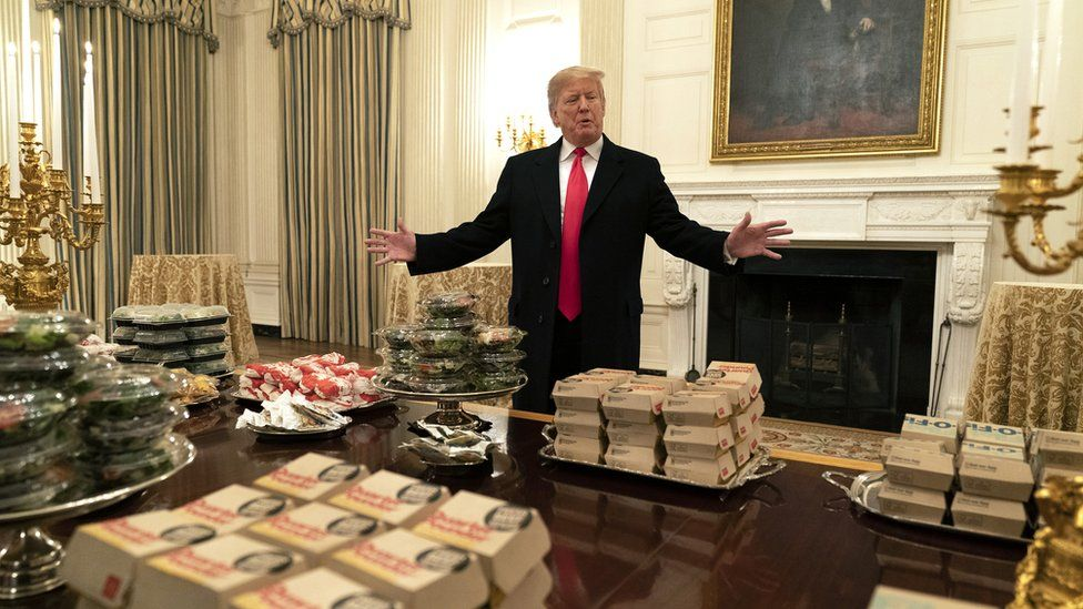 US President Donald Trump presents fast food to be served to the Clemson Tigers football team
