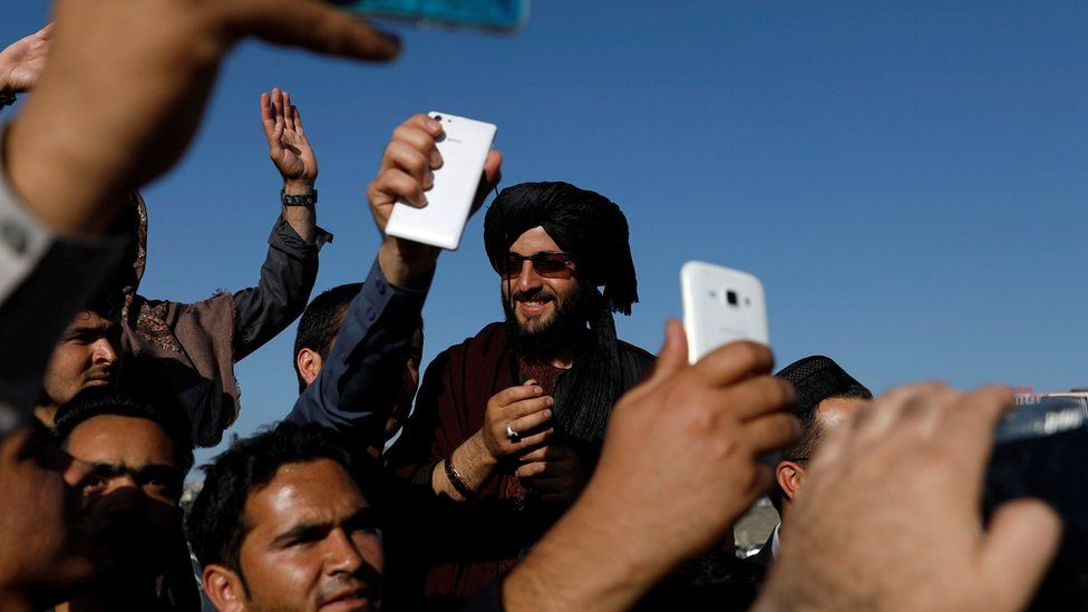 Afghans take pictures with a militant in Kabul
