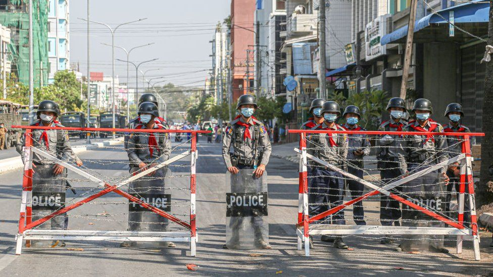 Police create a barricade and take guard on the road where protesters are protesting against the military coup.
