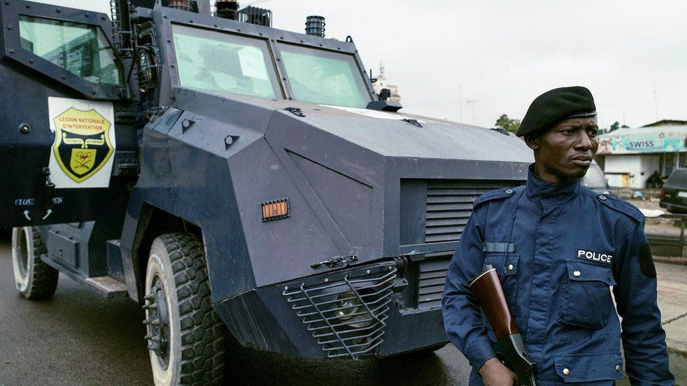policeman with a gun stands in front of anti-riot vehicle