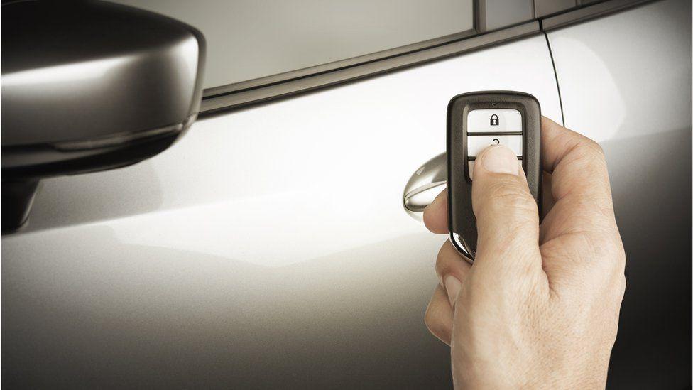A man using a Lexus remote to unlock his car