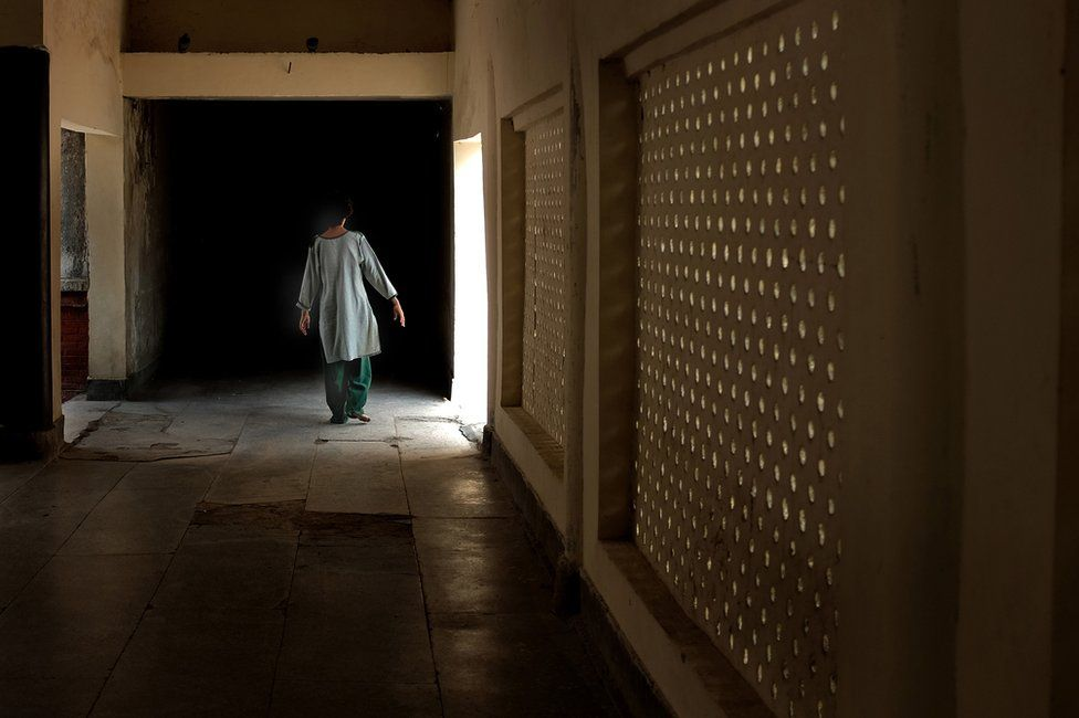 A woman, whose family institutionalised her when she displayed behavioural disorders, is seen walking down a corridor in the hospital.