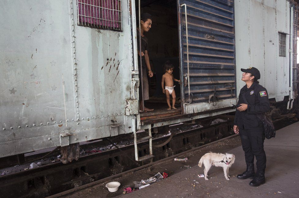 Sgt Lopez talks to a family in a railway carriage