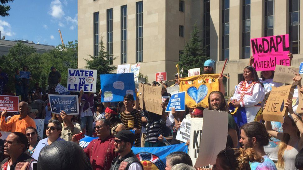 Protesters gather outside the US District Court while awaiting a judge's decision on whether to issue an injunction against the construction of the Dakota Access pipeline.