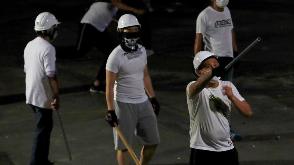 Men in white T-shirts with poles are seen in Yuen Long after attacked anti-extradition bill demonstrators at a train station, in Hong Kong, China July 22, 2019.