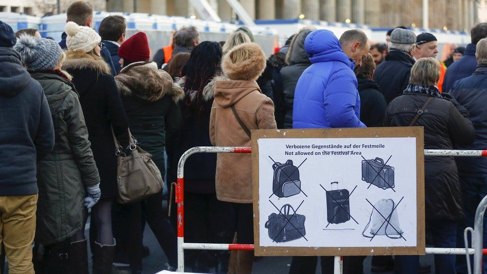 Visitors wait to pass the security check at the the fair grounds ahead the upcoming New Year's Eve celebrations, close to the Brandenburg Gate in Berlin, Germany, December 30, 2015.