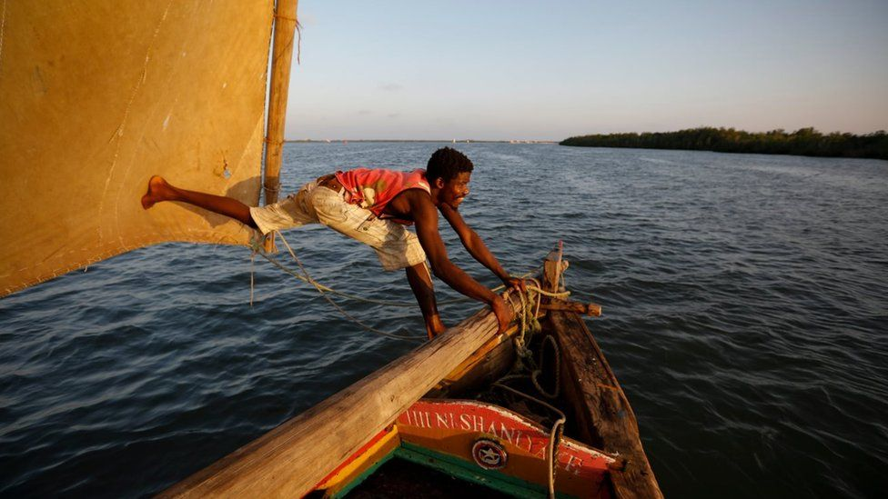 A man adjusting the mast on a dhow boat in south eastern Kenya.