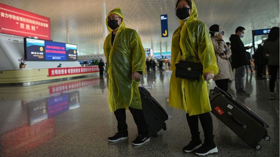 Passengers wearing protective gear walk at the Tianhe Airport after it was reopened today, in Wuhan in China's central Hubei province on April 8, 2020.