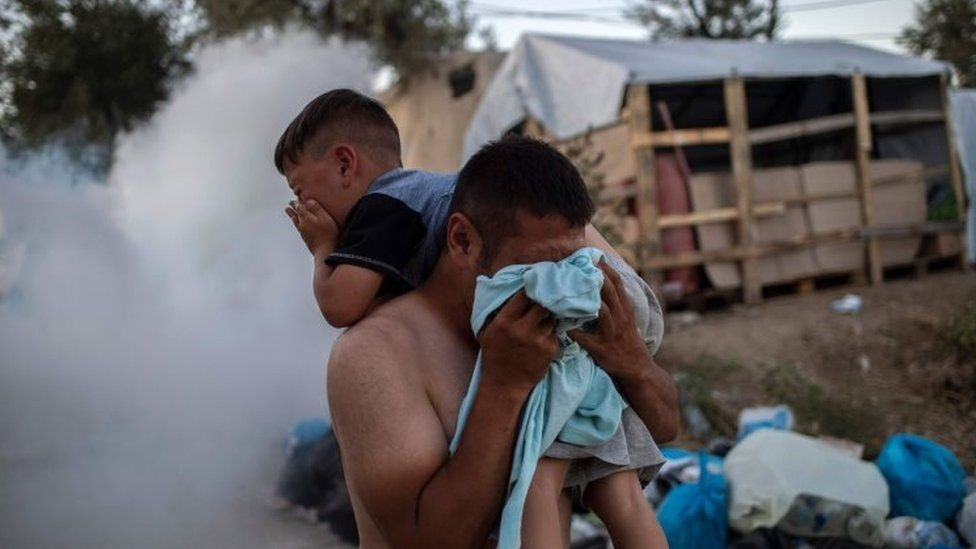 A refugee holds a boy and protects himself from tear gas fired by police at the Moria camp. Photo: 29 September 2019