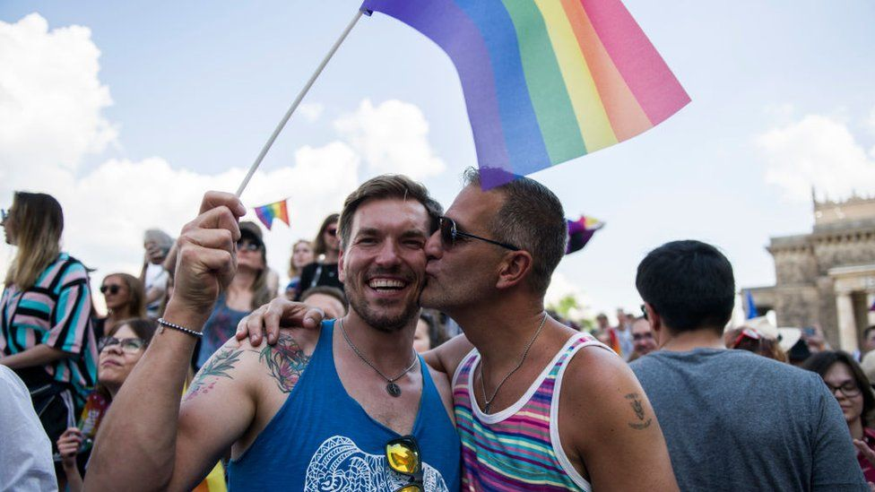 A gay couple seen kissing and waving the rainbow flag during the march