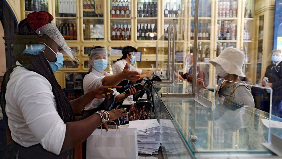 Staff wearing protective masks and face shields serve customers from behind screens at a café in Lisbon