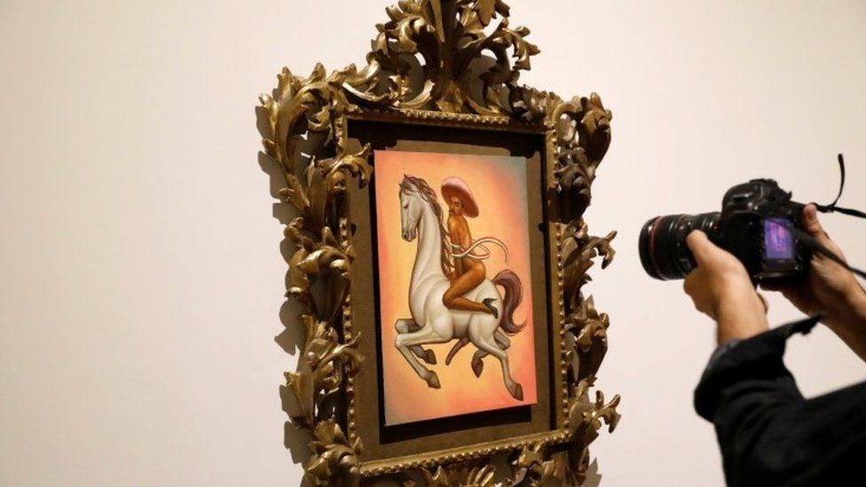 Man takes a photo of the Zapata painting