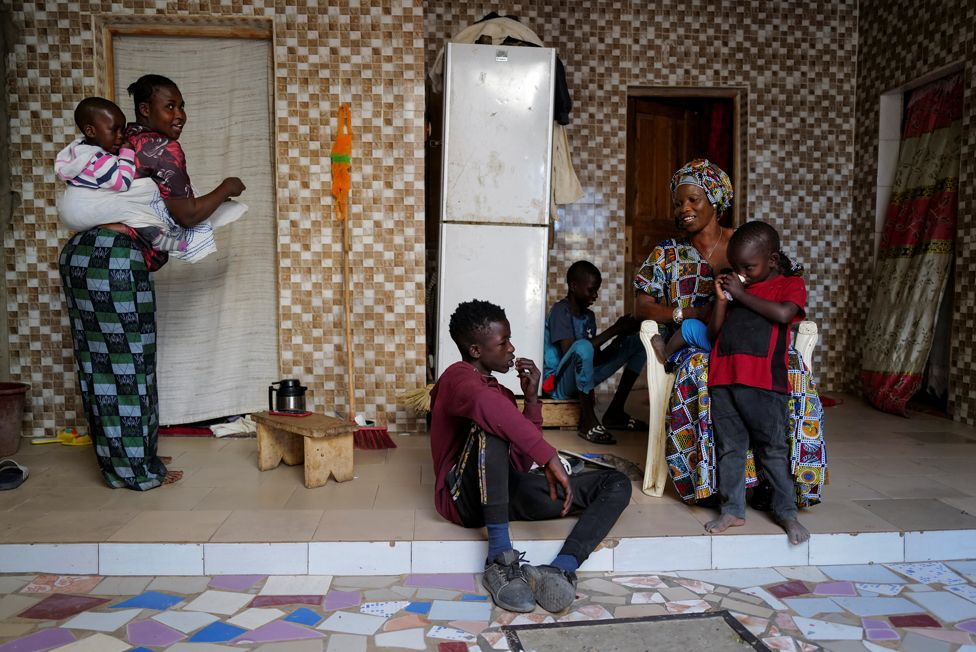 Fallou Diop sits next to his mother Ndeye Boye and brothers and sister, who is carrying her son, at their home in Niaga, Senegal, 28 January 2021