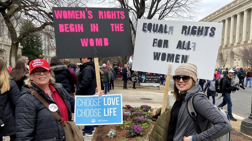 Protesters holding anti-abortion signs