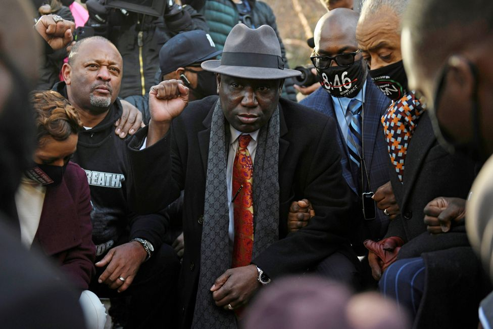 Attorney Ben Crump, Reverend Al Sharpton and the Floyd family kneel following a news conference outside the Hennepin County Government Center, on 29 March 2021