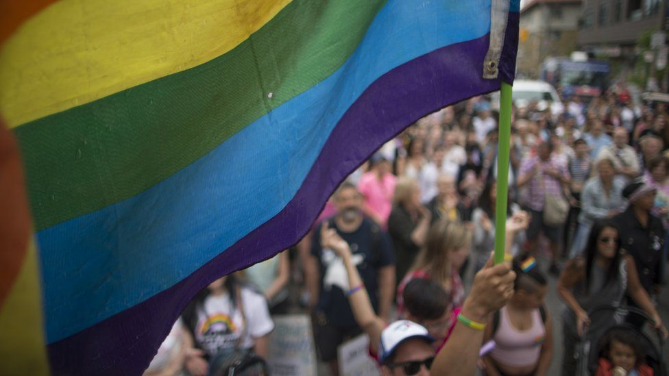 A man holds a pride flag at a rally in Toronto