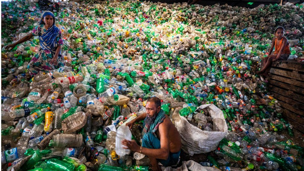Labourers sort through polyethylene terephthalate (PET) bottles in a recycling factory in Dhaka, Bangladesh, on May 5, 2021.