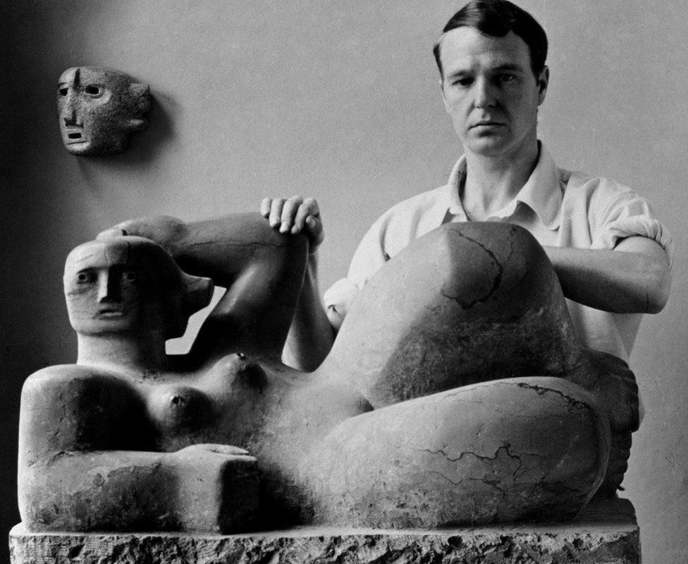 Henry Moore photographed with Reclining Figure