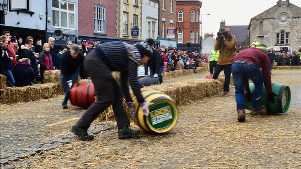 men rolling barrels