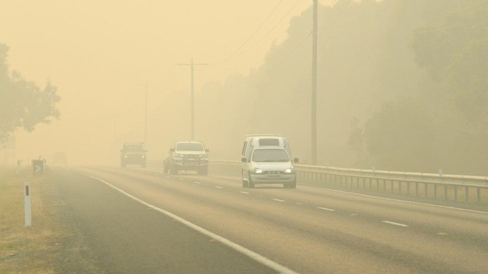 Cars evacuate through thick smoke caused by fires in Victoria
