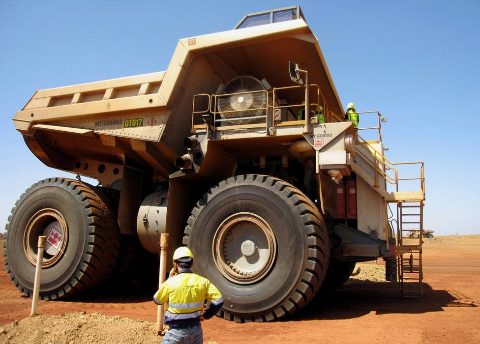 A worker stands before an iron ore tipper truck