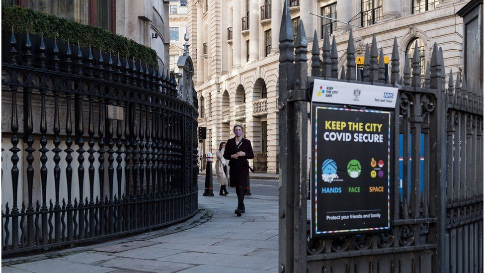 A person in a mask walks past a 'Keep the City Covid secure' sign