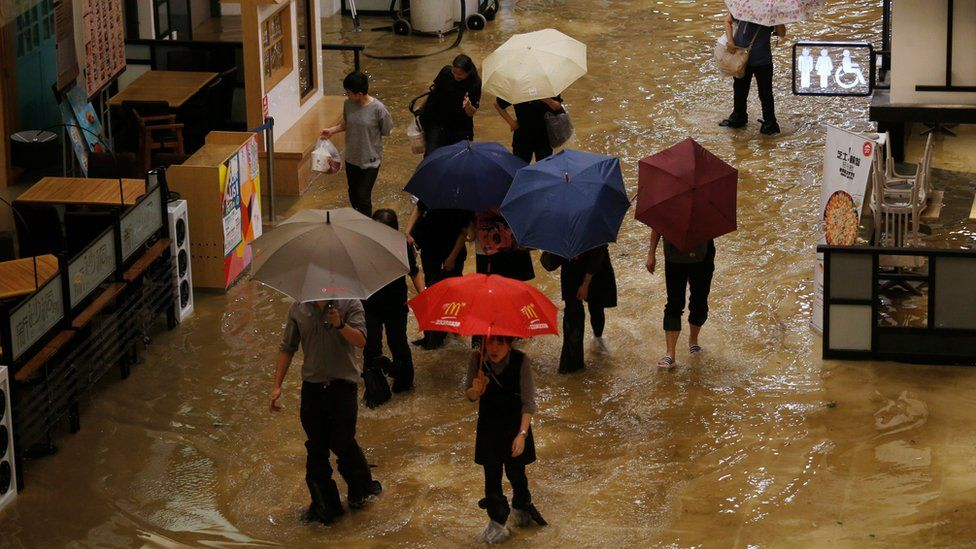 People wade through seawater inside a mall in Heng Fa Chuen, a residental district near the waterfront in Hong Kong, China September 16, 2018.