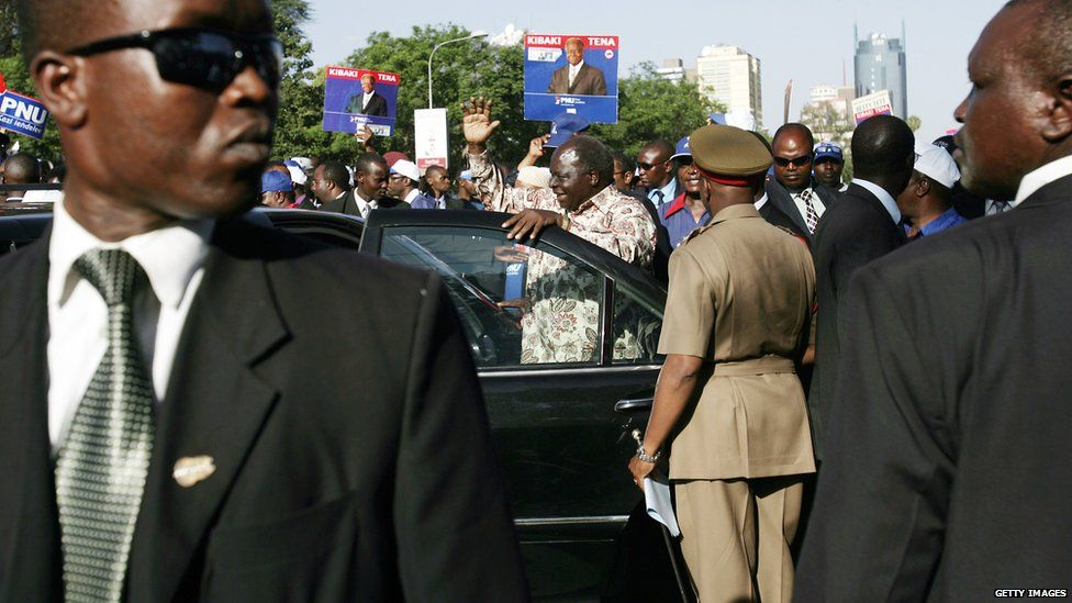 Kenyan President and presidential candidate Mwai Kibaki (C) waves to supporters before getting into his car surrounded with body guards after a rally in downtown Nairobi, 24 December 2007