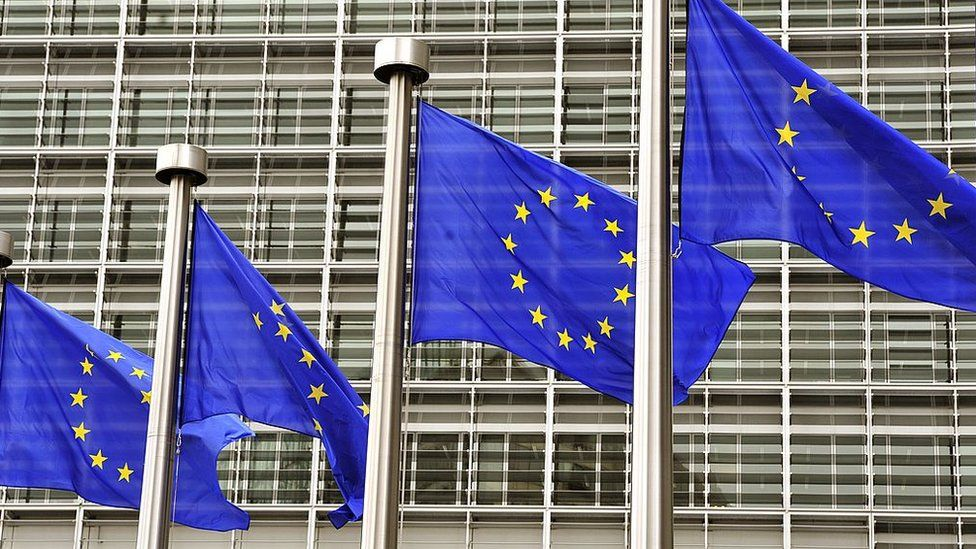 EU flags fly at the entrance to the EU Commission in Brussels