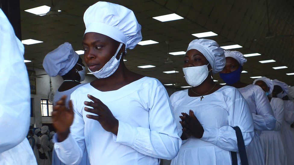 Women of the Celestial Church of Christ in white clothes, marching