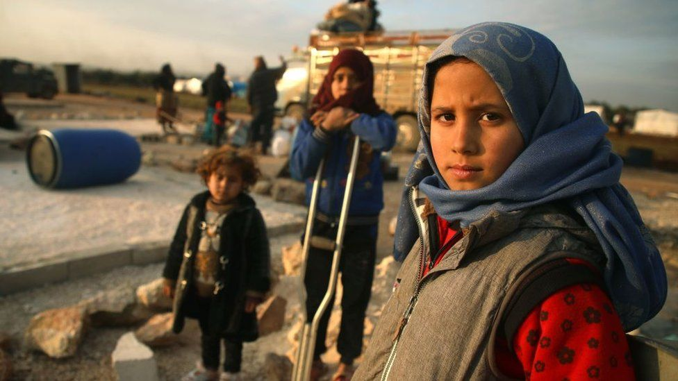 Syrian children prepare to flee a camp for the displaced, east of Sarmada, Idlib province (16 February 2020)