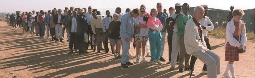 Well-heeled white people join with squatters to vote 28 April 1994 in South Africa's first multi-racial elections at the dusty Zevenfontein squatter camp, a northern Johannesburg suburb