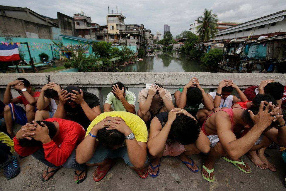 """Filipino men place their hands over their heads as they are rounded up during a police operation as part of the continuing """"War on Drugs"""" campaign of Philippine President Rodrigo Duterte in Manila, Philippines Friday 7 October 2016."""