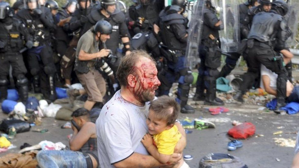 An injured migrant carries a child during clashes with Hungarian police. Photo: 16 September 2015