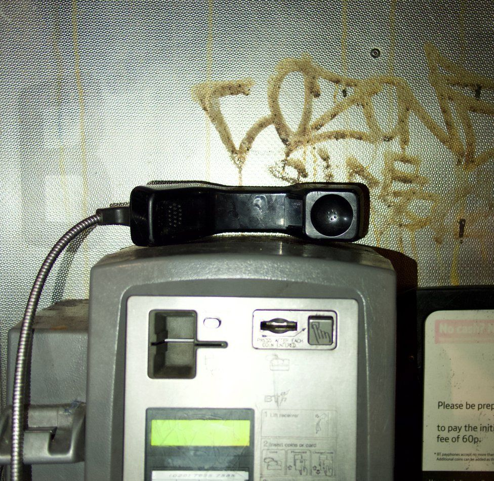 An image of a phone receiver in a public phone booth