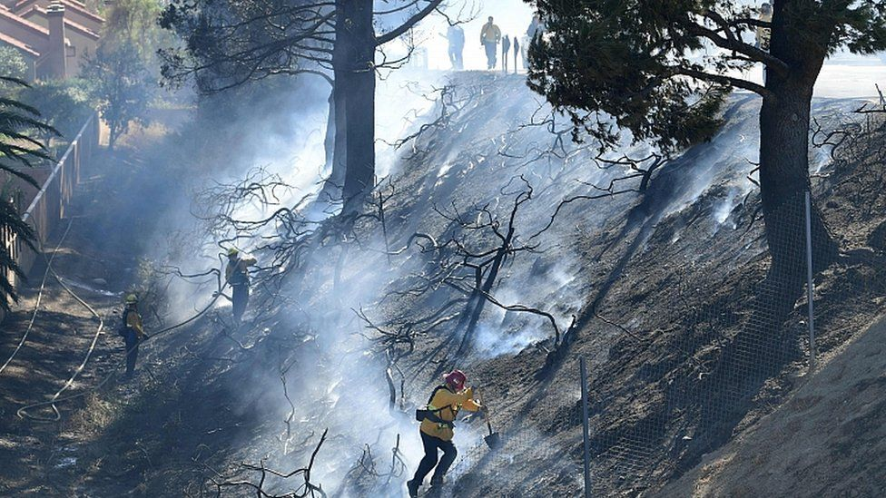 Firefighters work on a charred hillside near homes and the 118 Freeway in Simi Valley, California on October 30, 2019