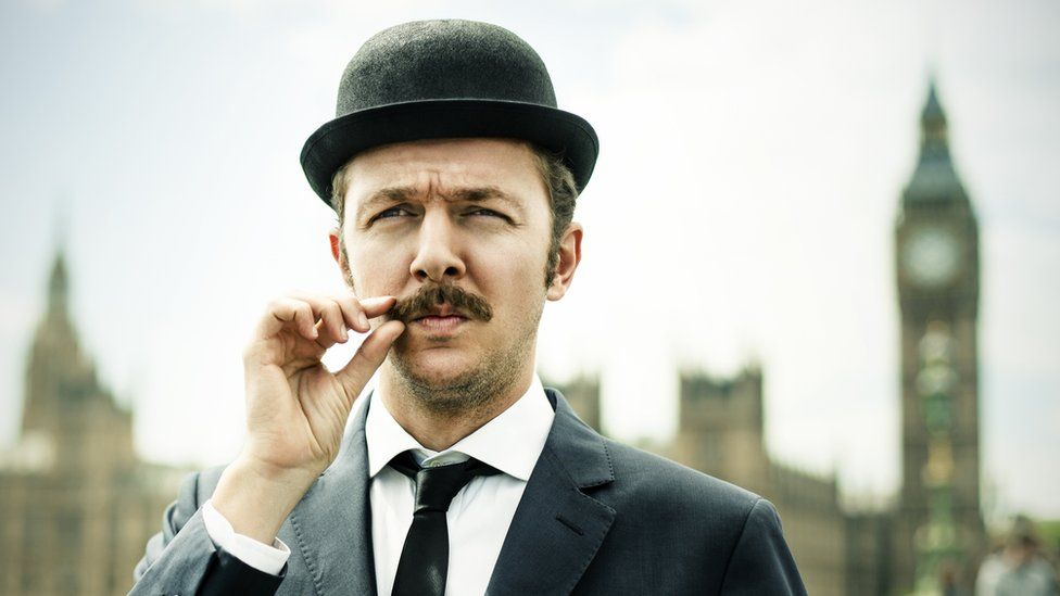 A man in a bowler hat twiddles his moustache