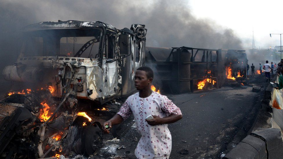 Passersby walk amid burned cars after an oil tanker exploded on a highway in Lagos, 28 June 2018