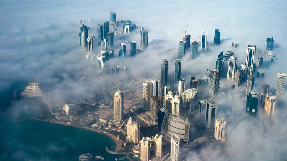An aerial view of high-rise buildings emerging through fog covering the skyline of Doha, as the sun rises over the city, in Doha, Qatar, 15 February 2014
