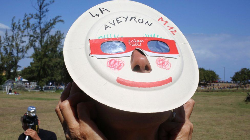 A woman looks through eclipse viewing glasses in Saint-Louis, on the island of La Reunion.