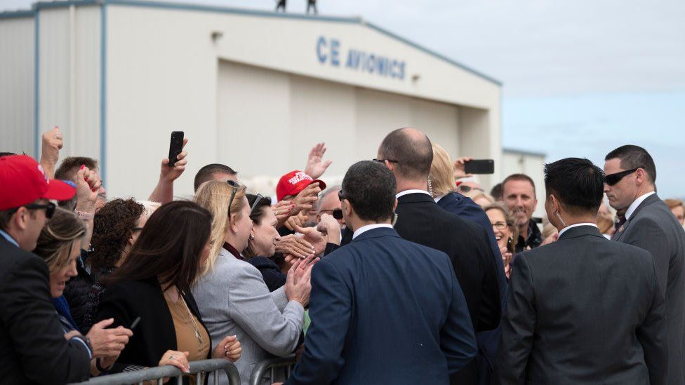 President Donald Trump shakes hands with supporters as he arrives in Orlando, Florida on 9 March