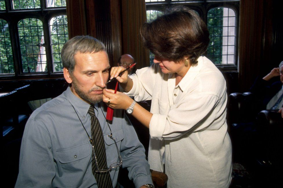 A make-up artist applies a grey wig and beard to Christopher Eccleston for one of the show's later episodes