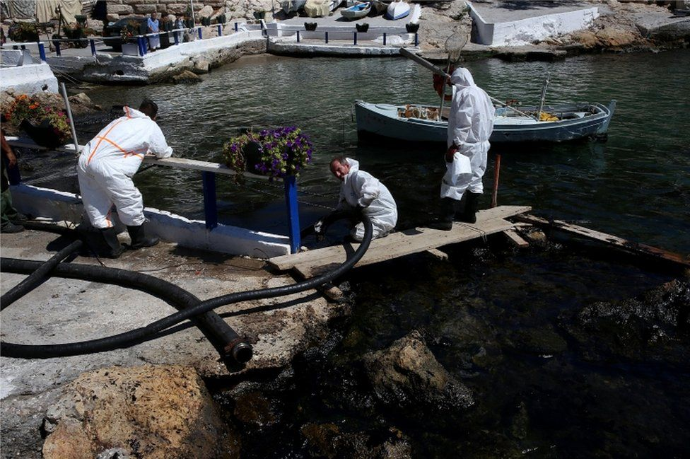 Workers deploy a hose to remove oil from a pretty bay near Athens on 13 September 2017