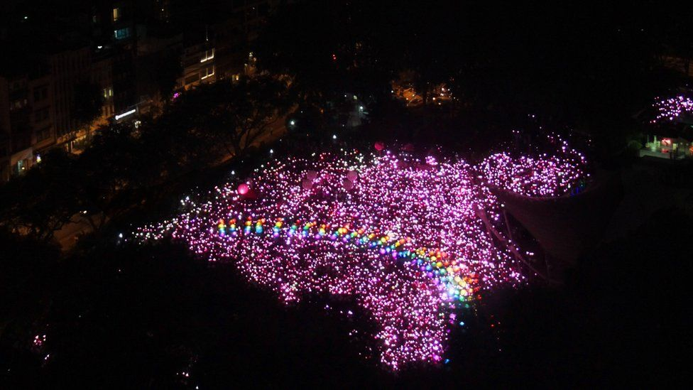 An aerial photo of the demonstration space in Singapore, filled with hundreds of pink lights in an irregular shape. Arcing across the centre is a series of coloured lights creating the image of a rainbow, a well-known LGBT symbol.