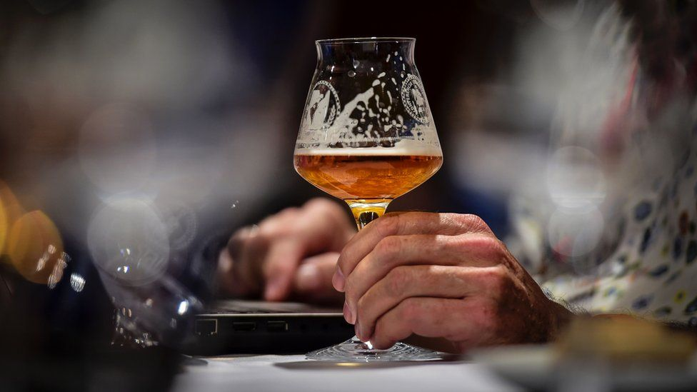A picture of a half-drank glass of craft beer in someone's hand